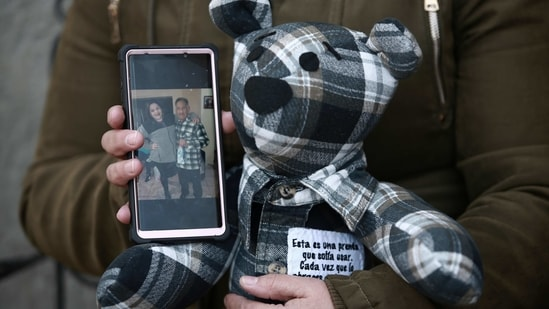Araceli Ramirez shows a stuffed bear she had made from the shirt of her father, Lorenzo Ramirez, who died so quickly from Covid-19 two months ago that she was unable to say goodbye, as she stands outside the home of bear maker Erendira Guerrero on January 11.(Christian Chavez / AP)