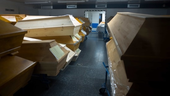 """The caskets are stacked three high in the Meissen crematorium's somber memorial hall, piled up in empty offices and stored in hallways. Many are sealed with plastic wrapping, others are labeled """"infection risk,"""" """"urgent"""" or simply """"COVID.""""(AP)"""