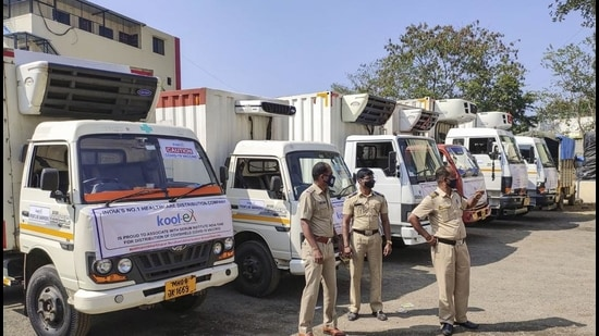 Police personnel guard the trucks to be used to transport the Covishield vaccine from Serum Institute of India to different parts of the country, in Pune on January 11. (PTI)