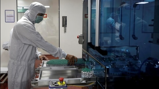 An employee in personal protective equipment handling vials of Covishield at Serum Institute of India, in Pune. (REUTERS)