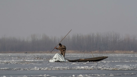 A Kashmiri fisherman aims a harpoon to catch fish in the frozen waters of Anchar Lake on the outskirts of Srinagar, (AP)