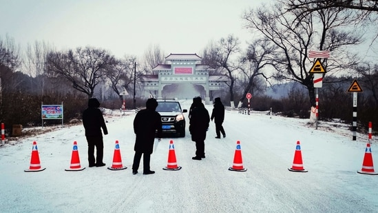 """Security personnel direct a commuter in Ang'angxi district as the province prepares to declare an """"emergency state"""" asking residents not to leave unless necessary in Qiqihar, Heilongjiang province, China on January 12. China recorded its biggest daily jump in Covid-19 cases in more than five months on January 13, stepping up containment measures that have seen four cities put under lockdown.(AFP)"""