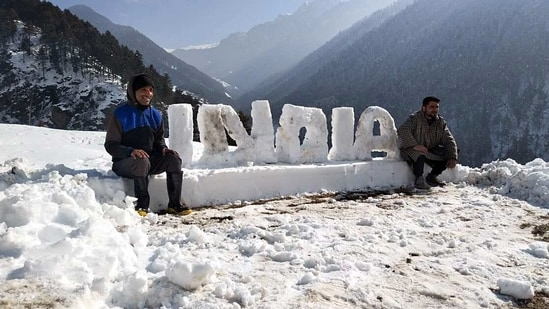 People pose for photos with India written with Snow, in Srinagar on Wednesday. (ANI Photo)