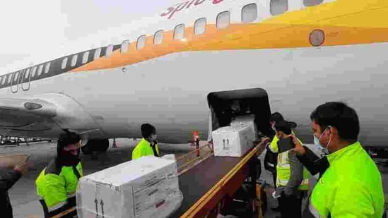 The first consignment of Covishield arrives at Indira Gandhi International (IGI) Airport in a special SpiceJet flight from Pune, in New Delhi on January 12. Flights from Pune transported the vaccine, developed by Oxford University and AstraZeneca, and is marketed in India as Covishield, to Delhi, Chennai, Kolkata, Guwahati, Shillong, Ahmedabad, Hyderabad, Vijayawada, Bhubaneswar, Patna, Bengaluru, Lucknow and Chandigarh, while three trucks left for Mumbai in the evening, HT reported.(HT Photo)