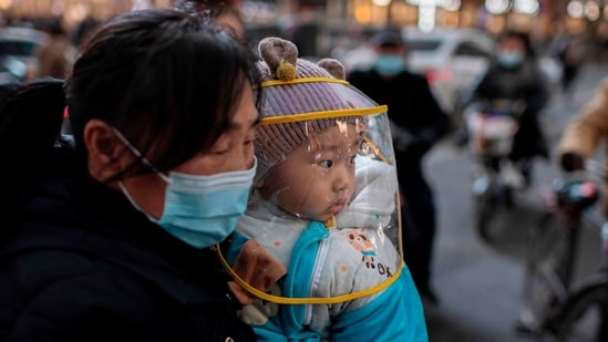A woman holds a child outside a shopping mall complex in Wuhan on January 13. While Wuhan was the initial epicentre of the novel coronavirus, which emerged there in late 2019, China had in recent months largely kept it at bay.(Nicolas Asfouri / AFP)