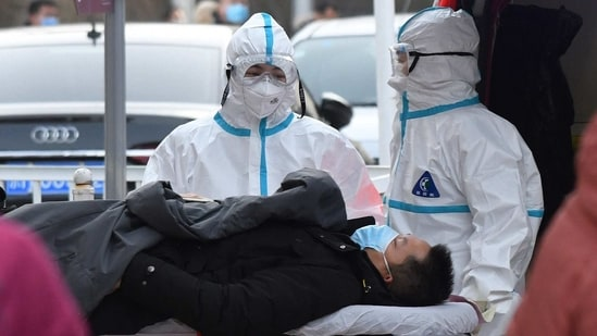 Medical workers wearing protective suits escort a patient to the fever clinic at a hospital in Beijing on January 13. The National Health Commission on January 13 reported a total of 115 new confirmed cases on the mainland, compared with 55 the previous day, the highest daily increase since July 30, Reuters reported.(Greg Baker / AFP)