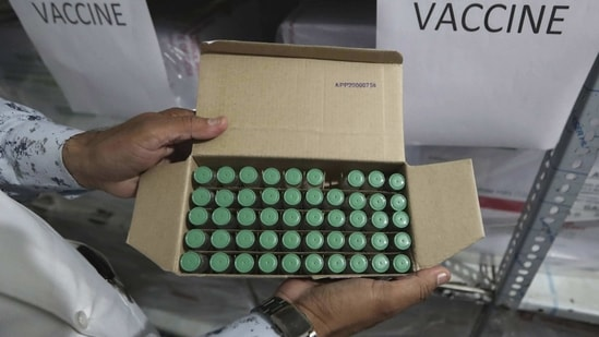 A health worker holds a box containing vaccines inside a cold storage centre at Civil Hospital in Ahmedabad on January 12. The Central government announced that all vaccine doses it has ordered, 11 million from Serum Institute and 5.5 million from Bharat Biotech, will be received by January 14 in all states and Union territories, HT reported.(Ajit Solanki / AP)