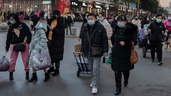 People wearing face masks seen during a rush hour in Wuhan on January 13. The spike in new cases comes as a World Health Organization (WHO) team of experts investigating the origins of the pandemic is set to arrive on January 14 in Wuhan. The team will have to spend 14 days in quarantine, Reuters reported citing NHC spokesman Mi Feng.(Nicolas Asfouri / AFP)