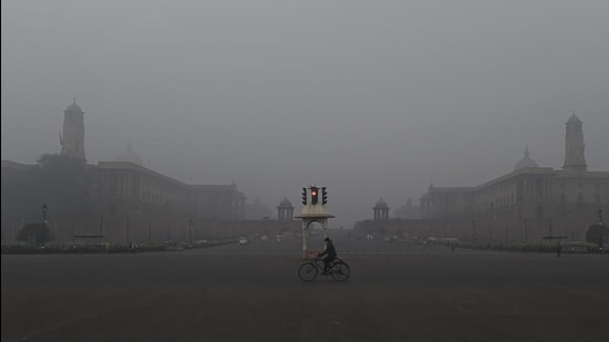 A man rides cycle near the Vijay Chowk, amid a cold and foggy winter morning in New Delhi on January 12. (PTI)