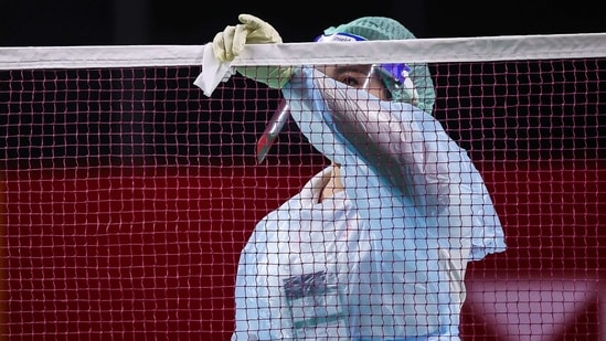 A Badminton Association of Thailand official wearing a face mask and shield while cleaning the net as a preventive measure against the spread of the Covid-19 coronavirus(AFP)