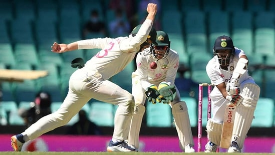 R Ashwin defends a ball as Tim Paine looks on(Getty)