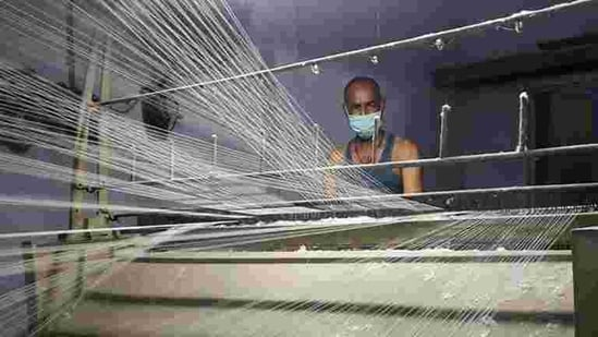 A worker wearing a protective face mask works on a loom in a textile factory, amidst the coronavirus disease (Covid-19) outbreak, in Meerut, India.(REUTERS)