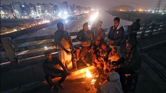 Farmers warm themselves around a bonfire on a cold evening at the Delhi-Ghazipur border. (File photo)
