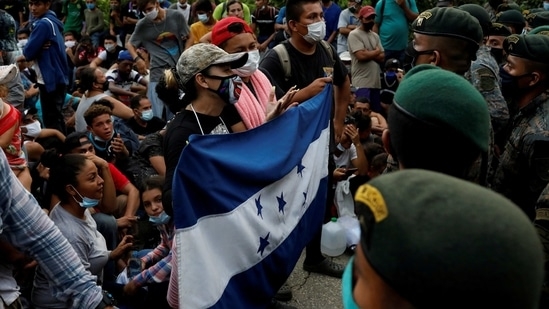 Honduran migrants trying to reach the US hold a Honduran flag while standing in front of Guatemalan soldiers blocking a road to stop migrants from reaching Mexico's border, in San Pedro Cadenas, Izabal, Guatemala.(Reuters/ File photo)