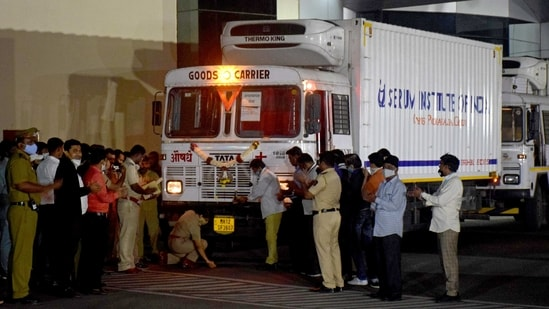 A police officer performs prayers in front of a truck carrying the first consignment of COVISHIELD, a coronavirus disease vaccine developed by AstraZeneca and Oxford University, before it leaves the Serum Bio-Pharma Park of Serum Institute of India in Pune on January 12. India is scheduled to begin its vaccination drive on January 16, which is set to be the largest globally.(Kalpesh Nukte / AP)