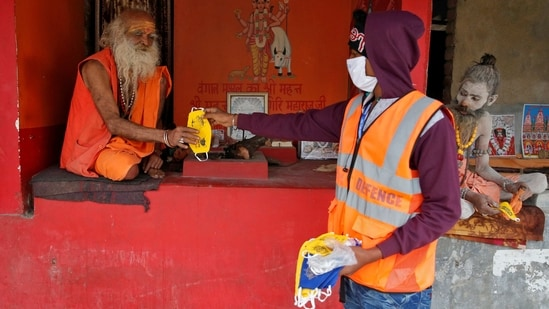 A man distributes face masks amongst sadhus ahead of Makar Sankranti festival at Sagar Island on January 13. Continuing with the trend of more daily recoveries from the disease than new cases, 17,652 more patients recovered in the last 24 hours, taking the total number of recovered cases to 10,146,763, the ministry's dashboard showed.(Rupak De Chowdhuri / REUTERS)