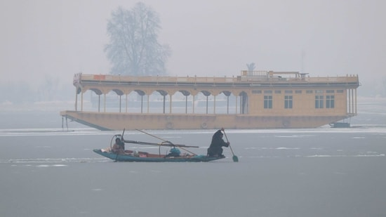 A Kashmiri boatman uses an oar to break the ice layer waters of Dal Lake after a snowfall, in Srinagar on Sunday. (ANI Photo)