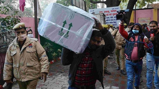 Workers unload the boxes of Covishield as first consignment of Covishield vaccine reach at storage facility centre, in Lucknow on Tuesday. (ANI Photo)