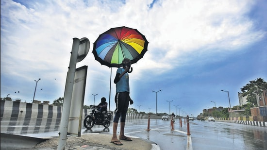 A man uses an umbrella to take shade from the rain in New Delhi on June 25, 2020 during the Covid lockdown. (Raj K Raj/HT PHOTO)