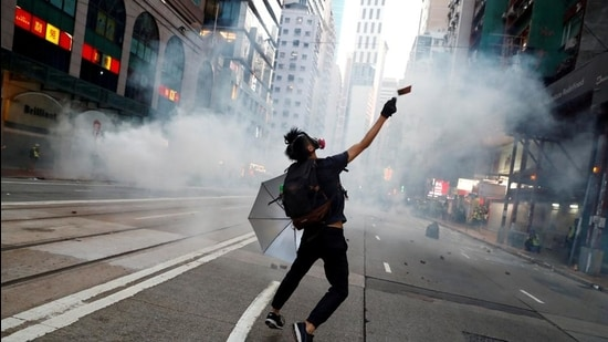 """An anti-government protester reacts as police fire tear gas during a march billed as a global """"emergency call"""" for autonomy, in Hong Kong on November 2, 2019. (REUTERS file)"""