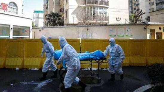 Medical workers move a person who died from Covid-19 at a hospital in Wuhan in central China's Hubei province. (AP/ File photo)