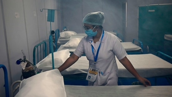 A medical staff arranges a bed after sanitization was done inside a makeshift isolation ward built to deal with suspected Covid-19 coronavirus patients as Hindu devotees gather at Sagar Island on January 12. India has logged 16,946 new infections in the preceding 24 hours, the ministry announced in its health update.(Dibyangshu Sarkar / AFP)
