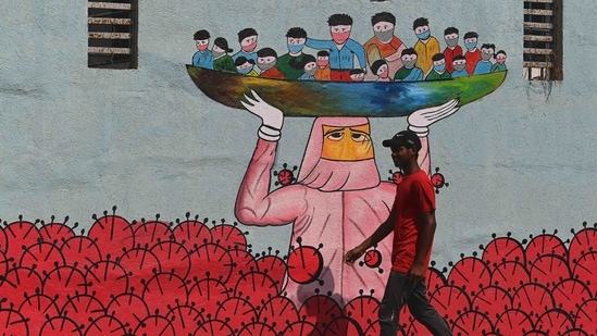 A pedestrian walks past a wall mural depicting on Covid-19, on January 13 in Mumbai. With this latest rise, India's tally of Covid-19 infections reached 10,512,093, the second-highest globally after that of the United States.(Indranil Mukherjee / AFP)