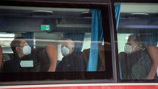 Members of the World Health Organization (WHO) team, including Peter Daszak (C) and Hung Nguyen (L), investigating the origins of the Covid-19 pandemic, board a bus following their arrival at a cordoned-off section in the international arrivals area at the airport in Wuhan on January 14, 2021. (AFP)