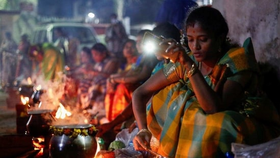 A devotee uses her mobile phone torch as she cooks a rice dish as devotees attend Pongal celebrations early morning on January 14, 2021.(Reuters)