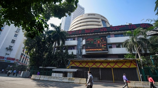 People look at the digital screen on the facade of BSE building in Mumbai.(PTI)