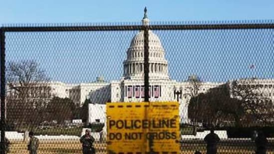 National guards are seen Wednesday, Jan. 13, 2021 on a fence that was erected to reinforce security at the Capitol in Washington. (AP)