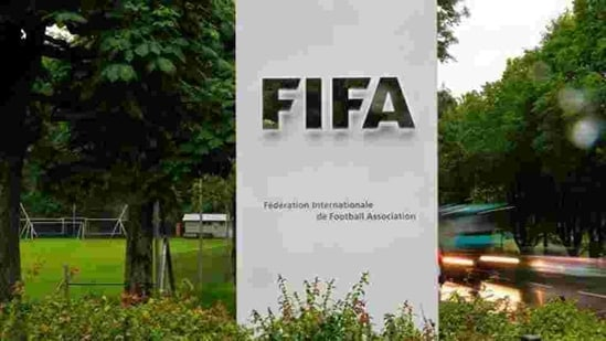 FILE PHOTO: Cars drive past a logo in front of FIFA's headquarters in Zurich(REUTERS)