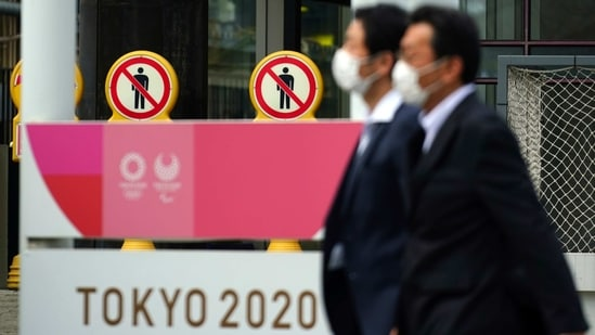 People wearing protective masks to help curb the spread of the coronavirus walk near a banner of Tokyo 2020 Olympics and Paralympic games in Tokyo Friday, Jan. 15, 2021. (AP)