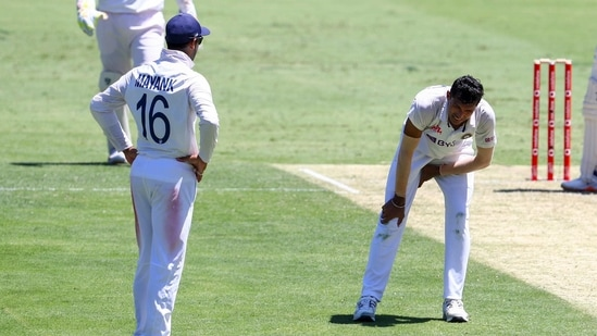 India's Navdeep Saini, right, reacts after injuring his leg while bowling during play on the first day of the fourth cricket test between India and Australia at the Gabba, Brisbane, Australia, Friday, Jan. 15, 2021. (AP)