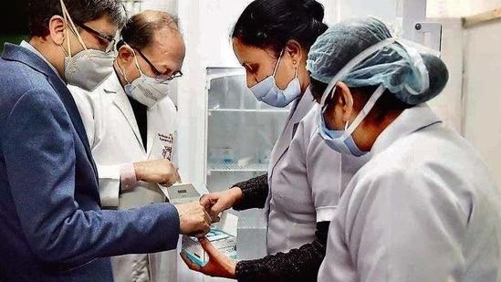 Medical professionals check vaccine vials at Kalawati Saran Children's Hospital