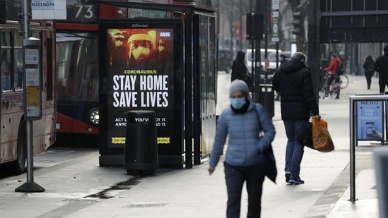 A coronavirus information sign is displayed by a bus stop in London. (AP Photo)