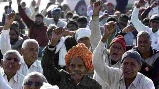 Farmers raise slogans during the ongoing protest against the new farm laws at Haryana-Rajasthan border.(HT Photo)