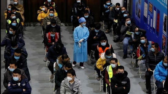 A medical worker walks next to people resting after receiving a dose of a coronavirus disease vaccine at a vaccination site, during a government-organised visit in Beijing on January 15. (Reuters)
