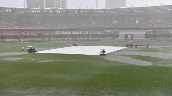 Water is seen pooling on the surface near the wicket during a rain delay on day two of the fourth test match between Australia and India at the Gabba.