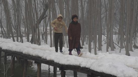 Children walk on a snow-covered wooden bridge amid dense fog during a cold winter morning, in Srinagar. (ANI Photo)