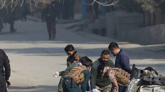 Afghan security officers carry out relief operation after a car bomb attack on Sunday.(AP Photo)