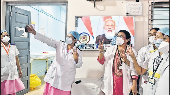 Health workers take a selfie during Prime Minister Narendra Modi's speech on the first day of a pan-India Covid-19 vaccination drive, at Rajawadi Hospital in Mumbai on Saturday. (Satish Bate/HT Photo)