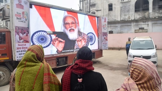 People watch the live telecast of Prime Minister Narendra Modi addressing the nation on the launch of Covid -19 vaccination drive, at District Hospital in Varanasi, Saturday, Jan. 16, 2021.(PTI)