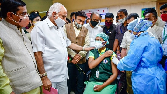 A medic administers the first dose of Covishield vaccine to a health worker in the presence of state CM BS Yediyurappa.(PTI)