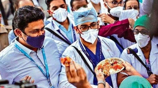 Employees welcome health workers carrying Covid vaccines at a hospital in Mumbai on Saturday.( Bloomberg)