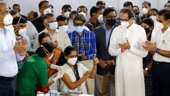 Madhura Patil, a health worker, gestures as she receives COVID-19 vaccine in the presence of Uddhav Thackeray, standing in white dress, Chief Minister of Maharashtra State in Mumbai, India, Saturday, Jan. 16, 2021. India started inoculating health workers Saturday in what is likely the world's largest COVID-19 vaccination campaign, joining the ranks of wealthier nations where the effort is already well underway. (AP Photo/Rajanish Kakade)(AP)