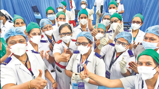 BMC medical staff congratulate their colleague senior staff nurse Charushila More after she administered the first Covid-19 vaccine shot at KEM Hospital, on Saturday. (Anshuman Poyrekar/HT Photo)