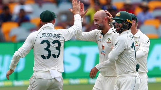 Australia's Nathan Lyon, left, is congratulated by teammate's Matthew Wade and Marnus Labuschagne, left, after taking the wicket of India's Rohit Sharma during play on day two of the fourth cricket Test between India and Australia at the Gabba, Brisbane, Australia, Saturday, Jan. 16, 2021.(AP)