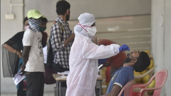 A healthcare worker collects swab sample of a resident in Mumbai. (HT Photo)