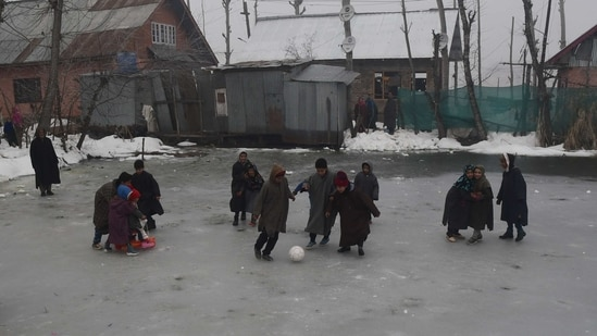 Children playing football on the frozen part of the Dal Lake during a cold winter morning in Srinagar.(PTI Photo)
